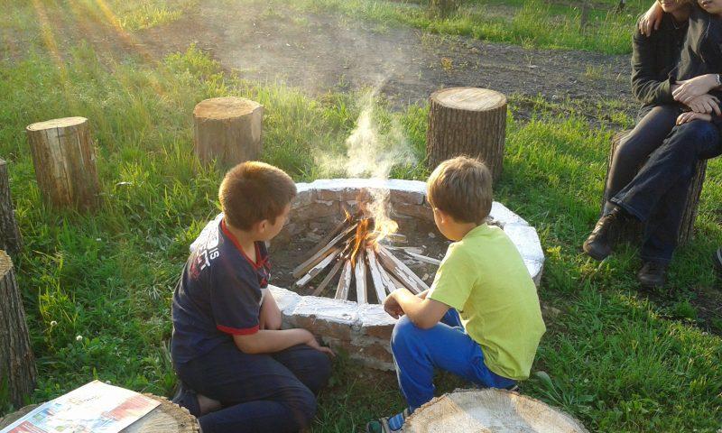 A képen tűz mellett szalonnázik két fiú a tábor helyszínén