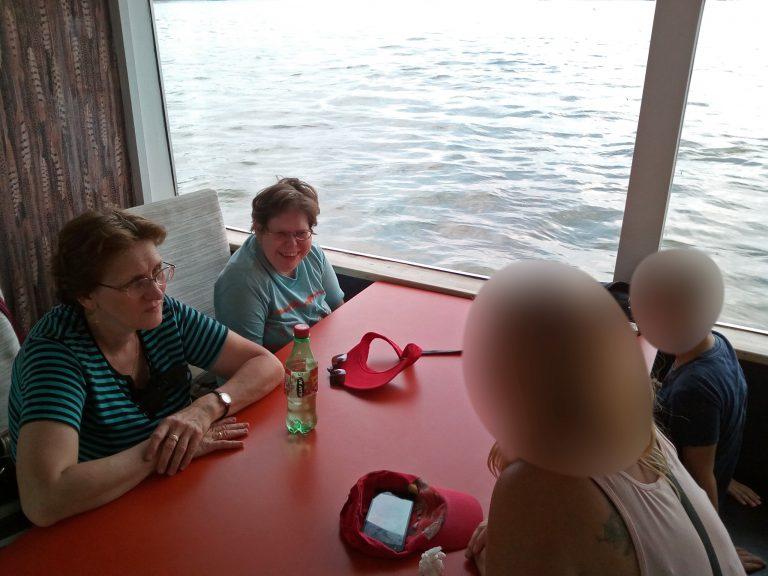 A képen az angyalföldi klubtagok beszélgetnek egy asztal mellett, háttérben a Duna látható