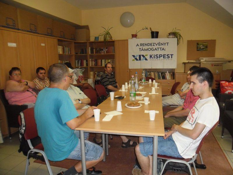 A kispesti klubnapon Tanai Csaba beszél a vakvezető kutyákról, a klub tagjai egy asztal körül ülve hallgatják őt