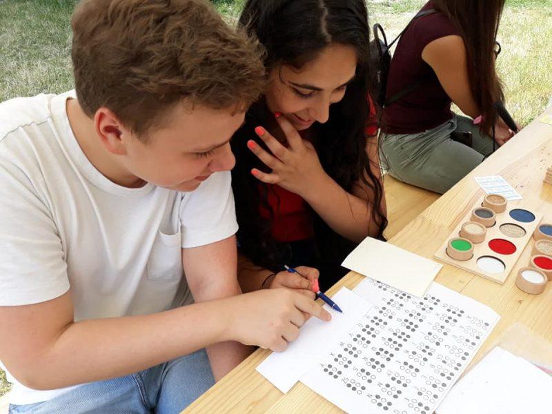 egy pár ismerkedik a Braille-írással a ferencvárosi klub asztalánál a prevenciós napon