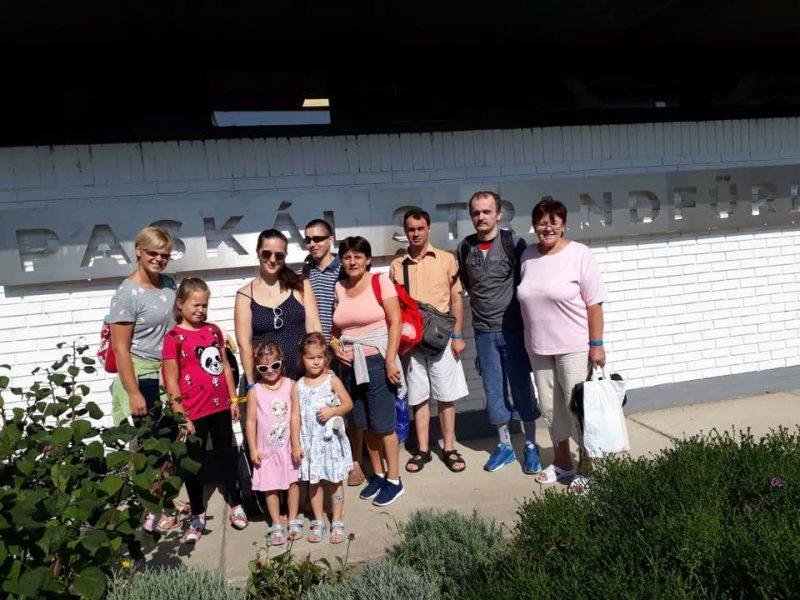 A Klub tagjai a strand bejárata előtt állnak