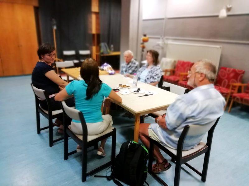 A képen a kőbányai klubtagok láthatóak, amint egy asztal mellett ülve hallgatják Pál Szilviát