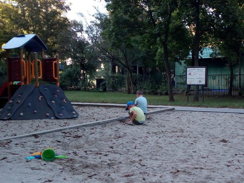 A képen két kisfiú látható, akik a homokozóban játszanak egymással