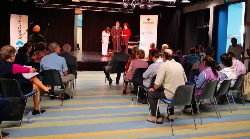 A zuglói fehér bot napi ünnepségen Fodor Ágnes, a VGYKE elnöke, Pál Zsolt (Pille), a Vakrepülés színtársulat tagja és Kiss Márta, zuglói közösségi civilszervező áll a színpadon