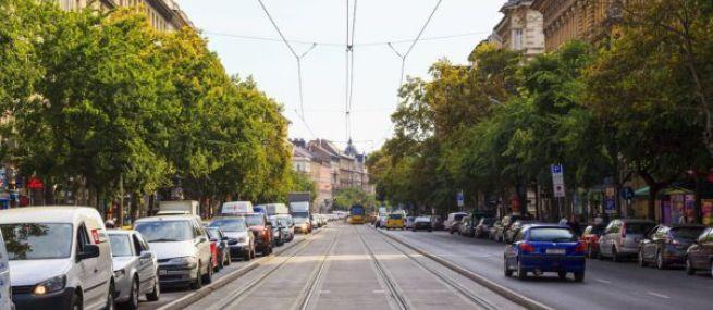 A képen a Nagykörút egyik szakasza látható, két oldalt fákkal, középen a villamos és a vágányok