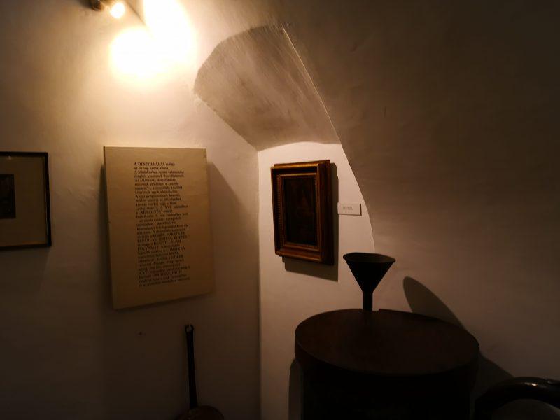 A patikamúzeum belső tere látható a képen, festményekkel és tárgyakkal teli sarok
