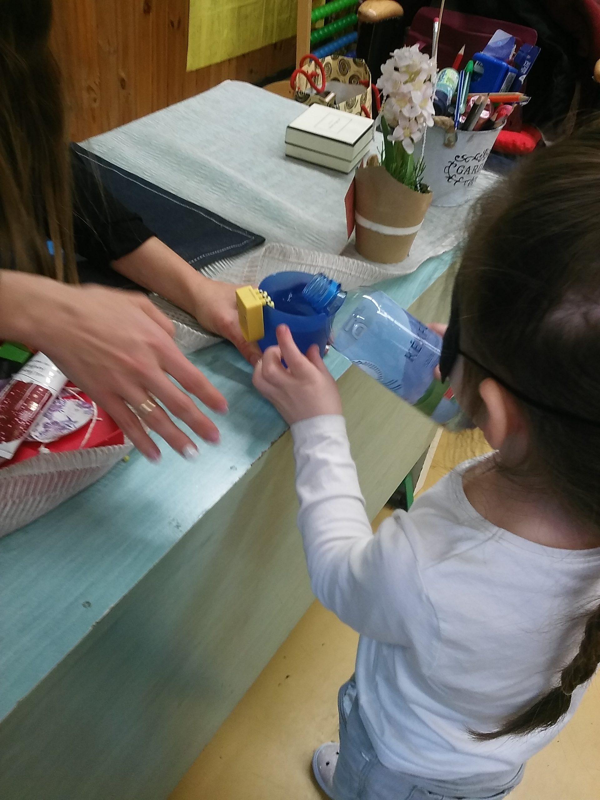 Egy kislány vizet tölt egy pohárba.