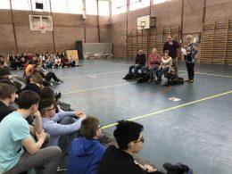A diákok figyelik az előadást az iskola tornatermében.