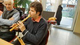 Domoszlai János látható a képen, aki a kenát (hangszer) mutatja be.