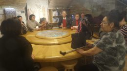A tagok az asztalnál ismerkednek a tárlatvezetővel.