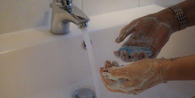 A képen egy fürdőszobai csapból folyó víz előtt egy besszappanozott kéz látható.