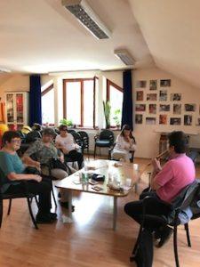 A képen a klubtagok Domoszlai Jánost hallgatják, aki zenél.