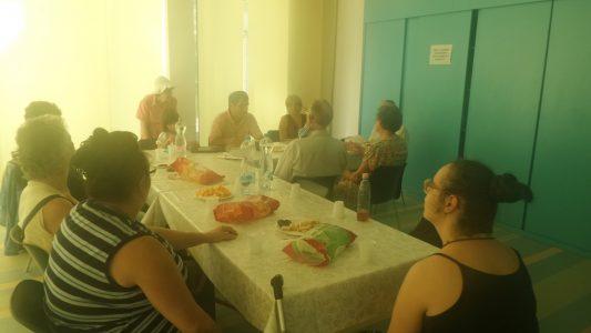 A klubtagok az asztal körül ülnek.