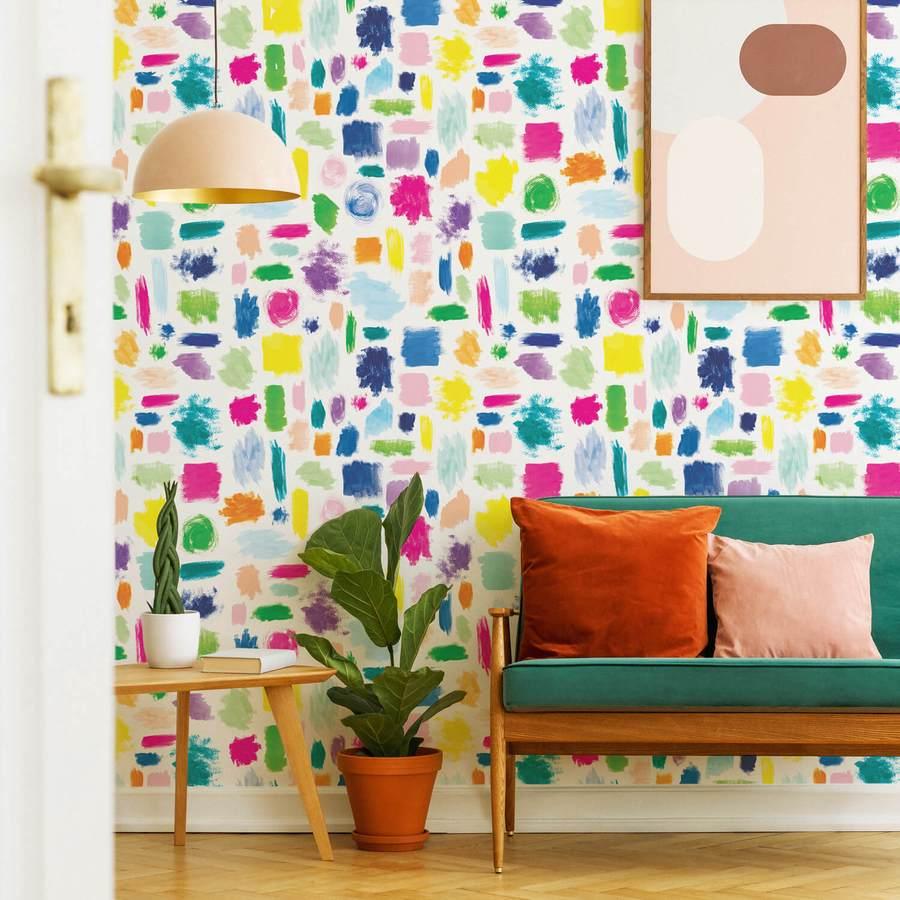 A képen egy szoba látszik néhány bútorral, falai fehér alapon színesre festve.
