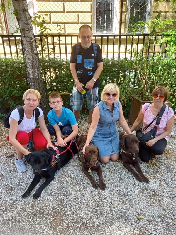 A képen az érzékenyítő csapat tagjai és vakvezető kutyáik láthatók.