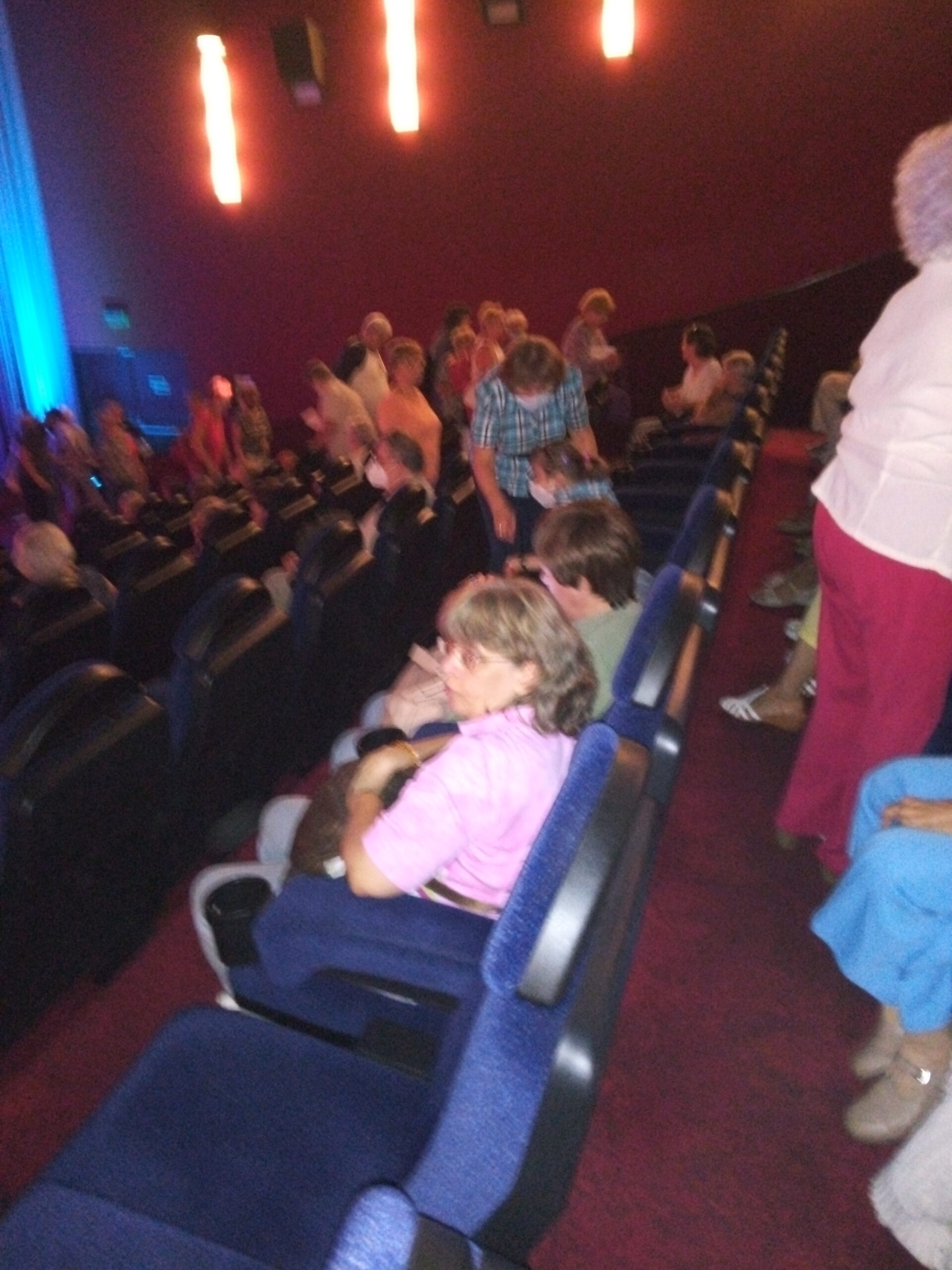 A közönség helyet foglal a nézőtéren.