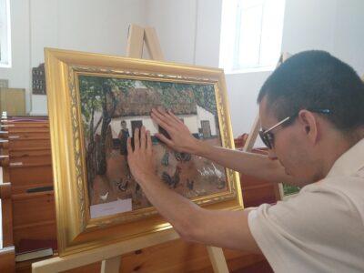 Juhos Róbert az egyik festményt tapintja.