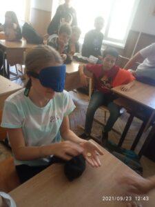 A diákok a pénzfelismerést próbálják ki bekötött szemmel.