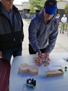 A képen két úr látható, egyikük bekötött szemmel játszik a tapintós játékkal.