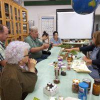 Az asztal körül a csoport tagjai és a múzeumpedagógus, az asztalon gyógy-és fűszernövények láthatók.