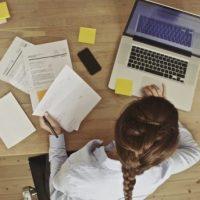 A képen egy hölgy látható, amint egy asztalnál ül, papírral a kezében és a laptopján dolgozik