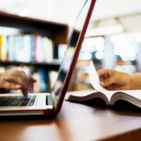 A képen egy laptop látható asztalon, melyen valaki dolgozik